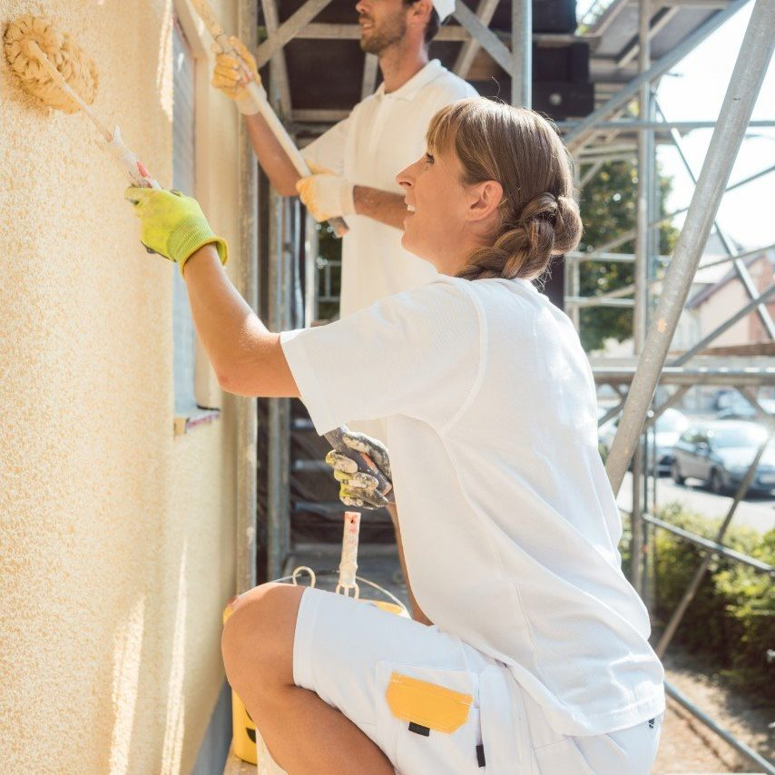 Picture of two painters in white painting a home exterior.