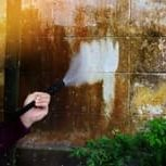 Picture of a person pressure washing brown dirt off of a white building.